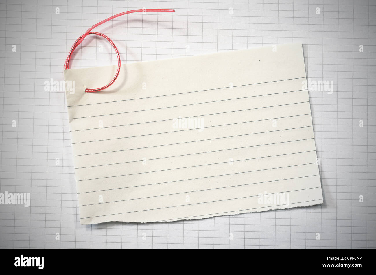 torn lined paper with red wire in shape of number six over