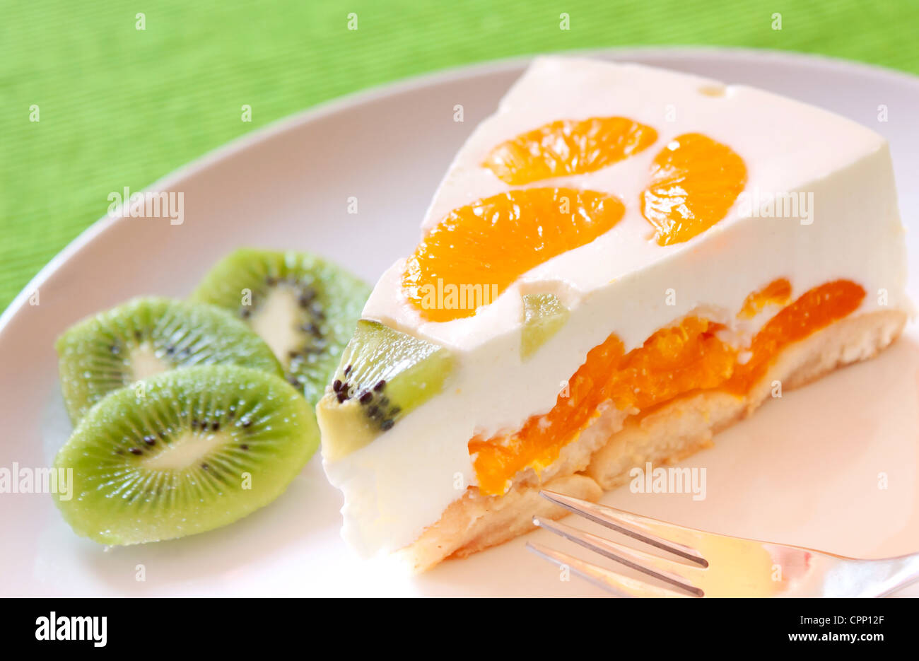 A delicious cake with clementine and kiwi on a bed of biscuits - Stock Image