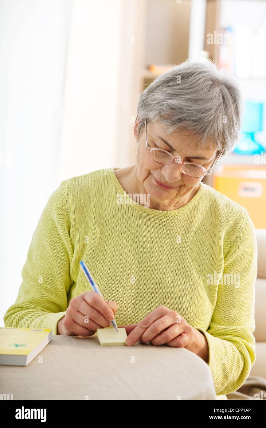 ELDERLY PERSON WRITING - Stock Image