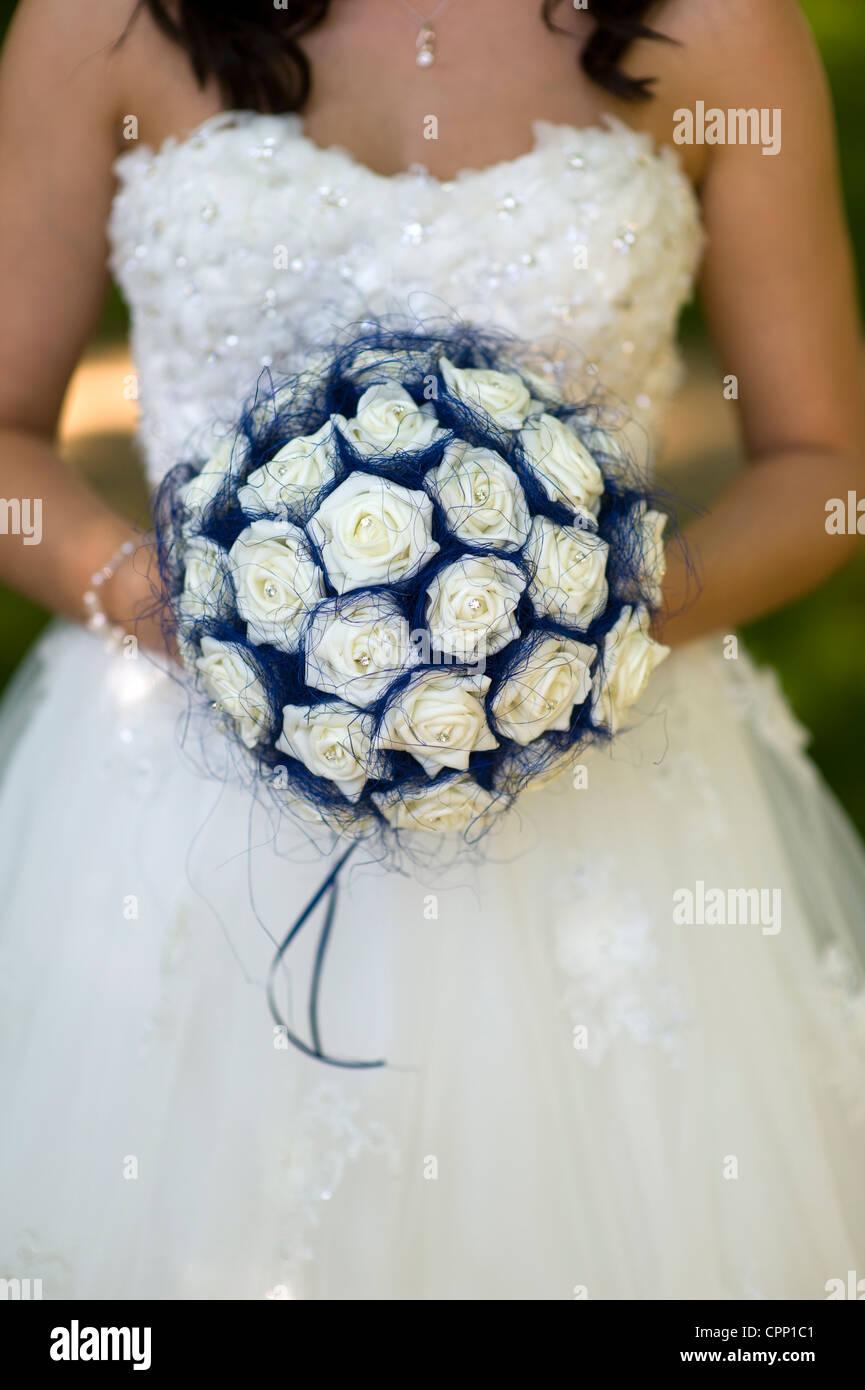 bride holding imitation flower bouquet - Stock Image
