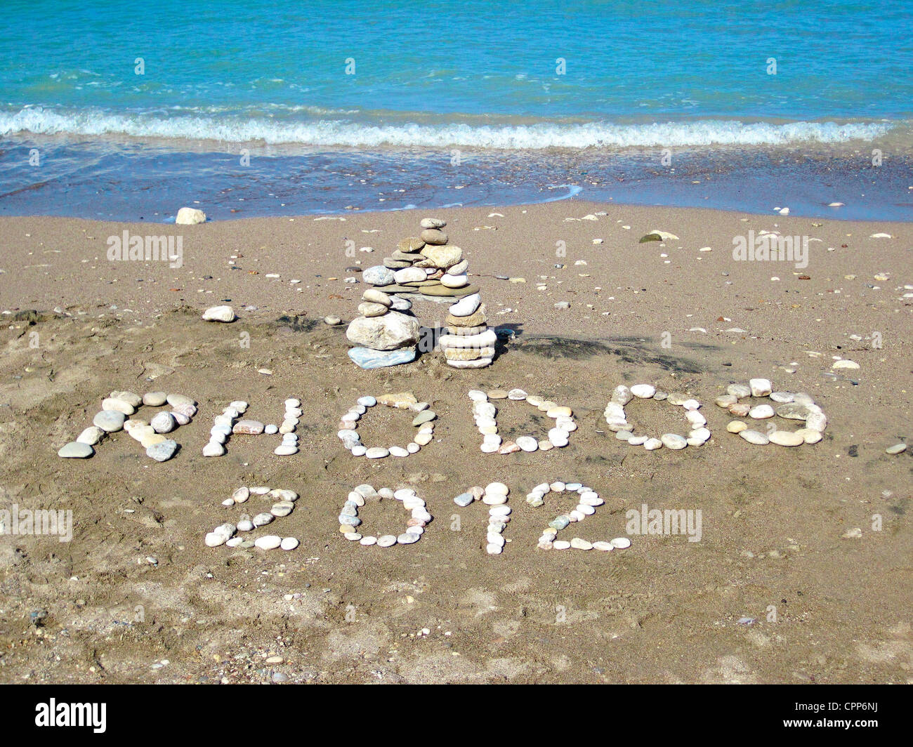 Rhodos 2012 spelt out using stones on Afandou beach, Rhodes Greece - Stock Image