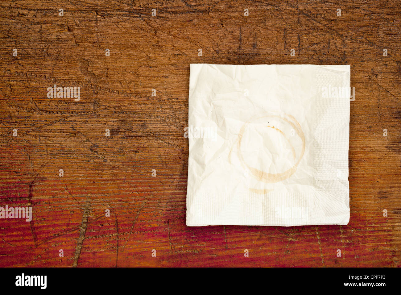 napkin with coffee stains on a grunge scratched wooden table - Stock Image