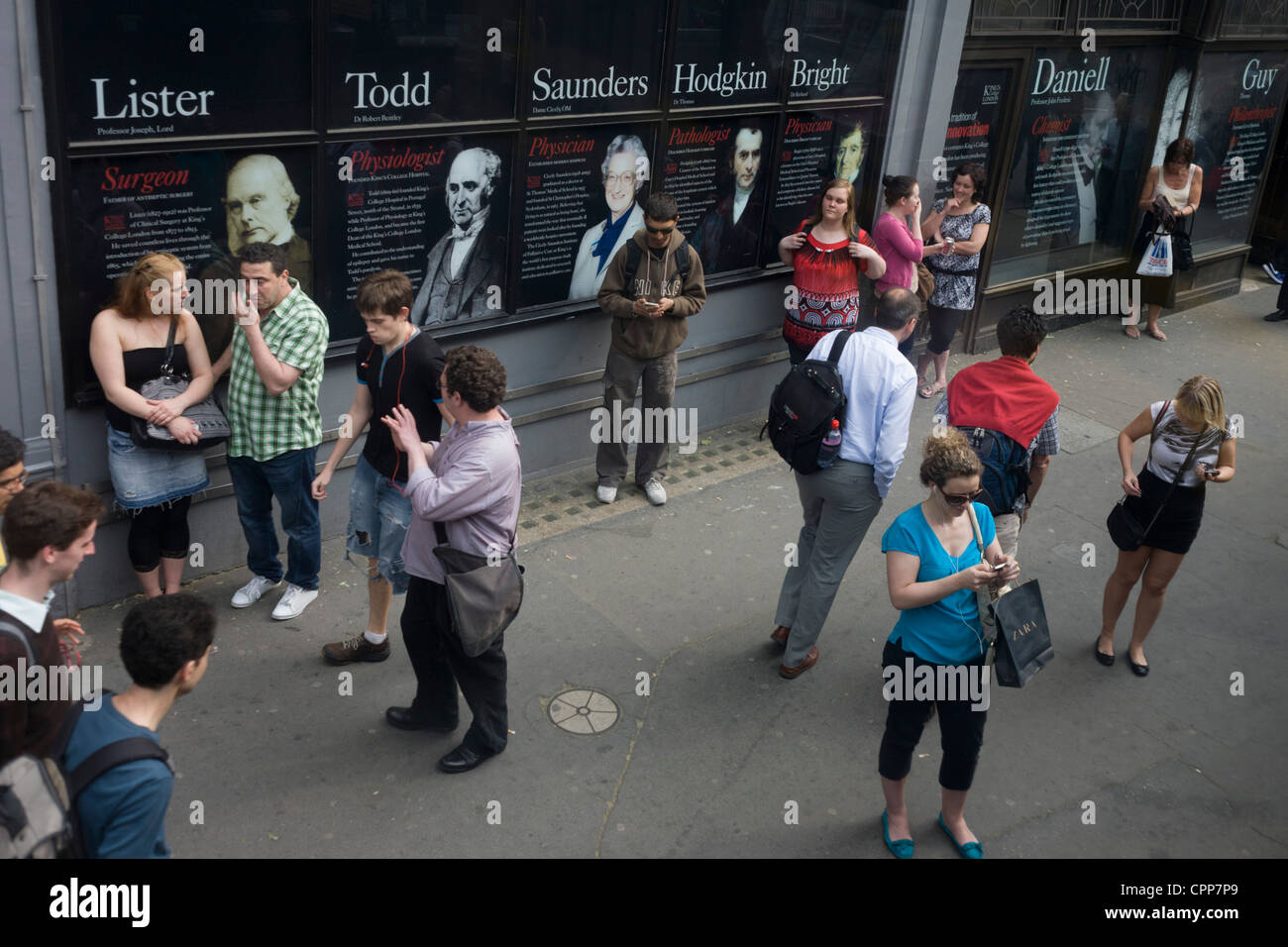 Aerial view of commuters at a city bus stop outside King's College on the Strand, whose alumni faces and names - Stock Image