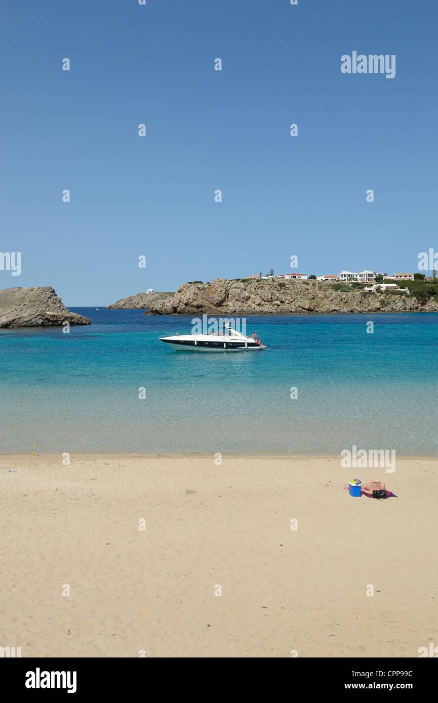 lone sunbather on the beach arenal d'en castell menorca spain - Stock Image