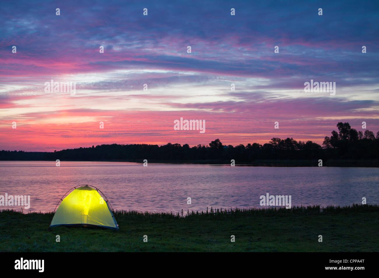 Lakeshore camp at dawn - Stock Image