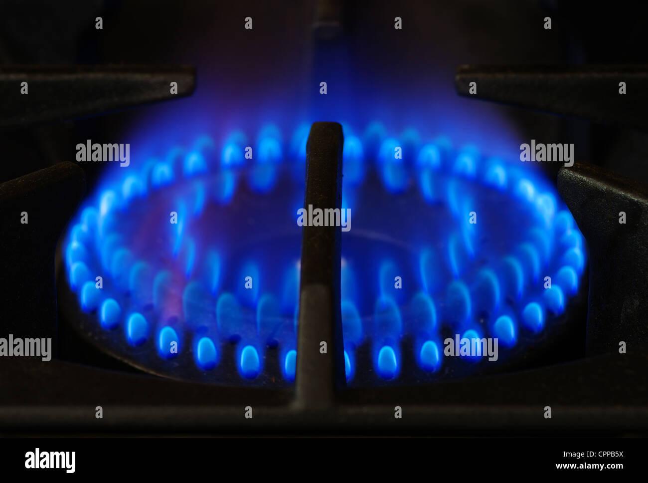 gas stove range burner with dark metal grate - Stock Image