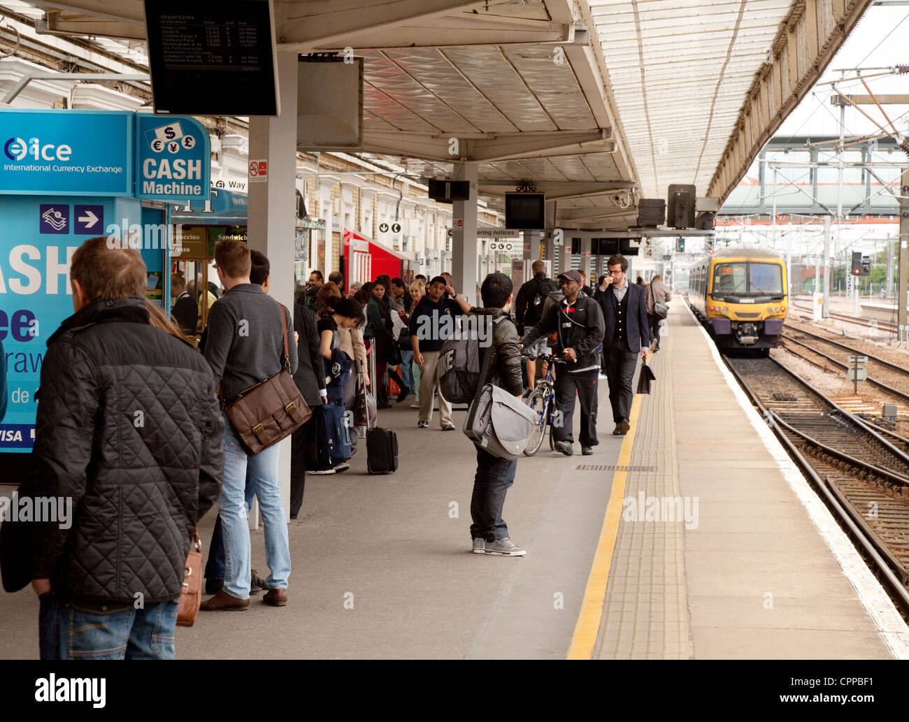 Rail travellers waiting for a train on the platform at Cambridge station, Cambridgeshire UK - Stock Image
