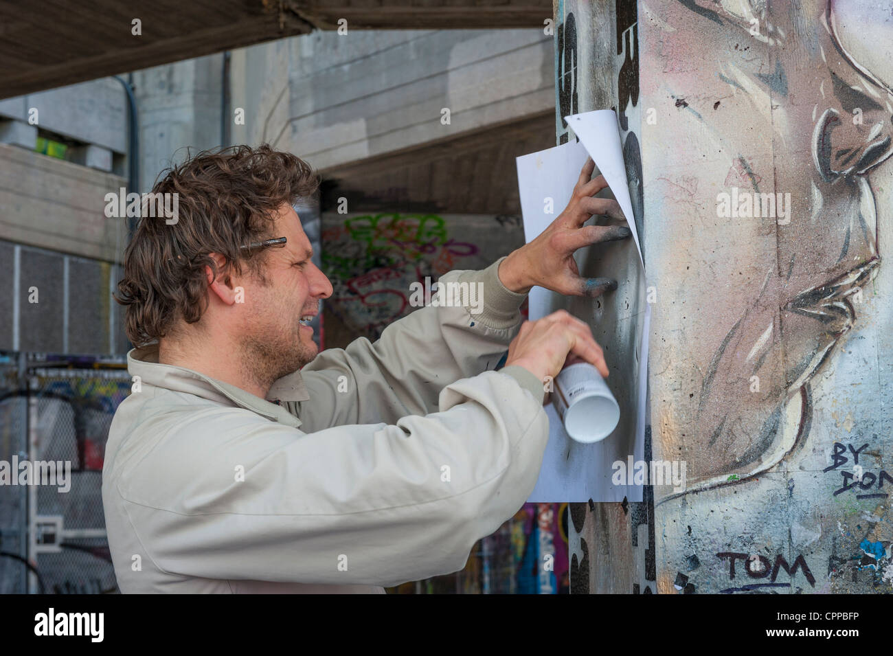 London , Southbank , Riverside , Embankment , street artist Don spray can painting graffiti mural picture black - Stock Image