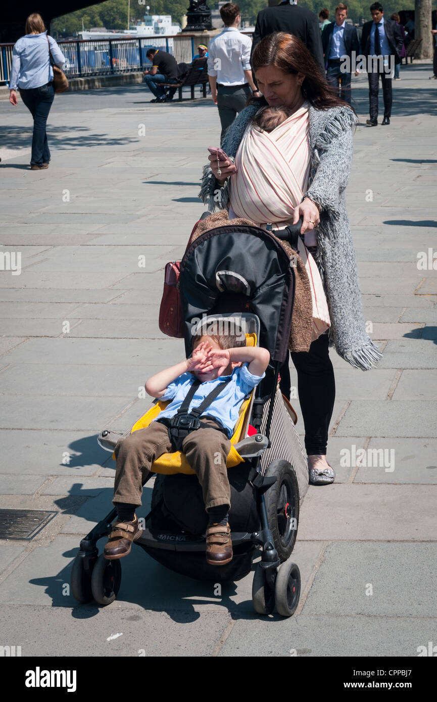 London , Southbank , Riverside , Embankment , mother infant in buggy pram pushchair & baby in shawl rebozo sling - Stock Image