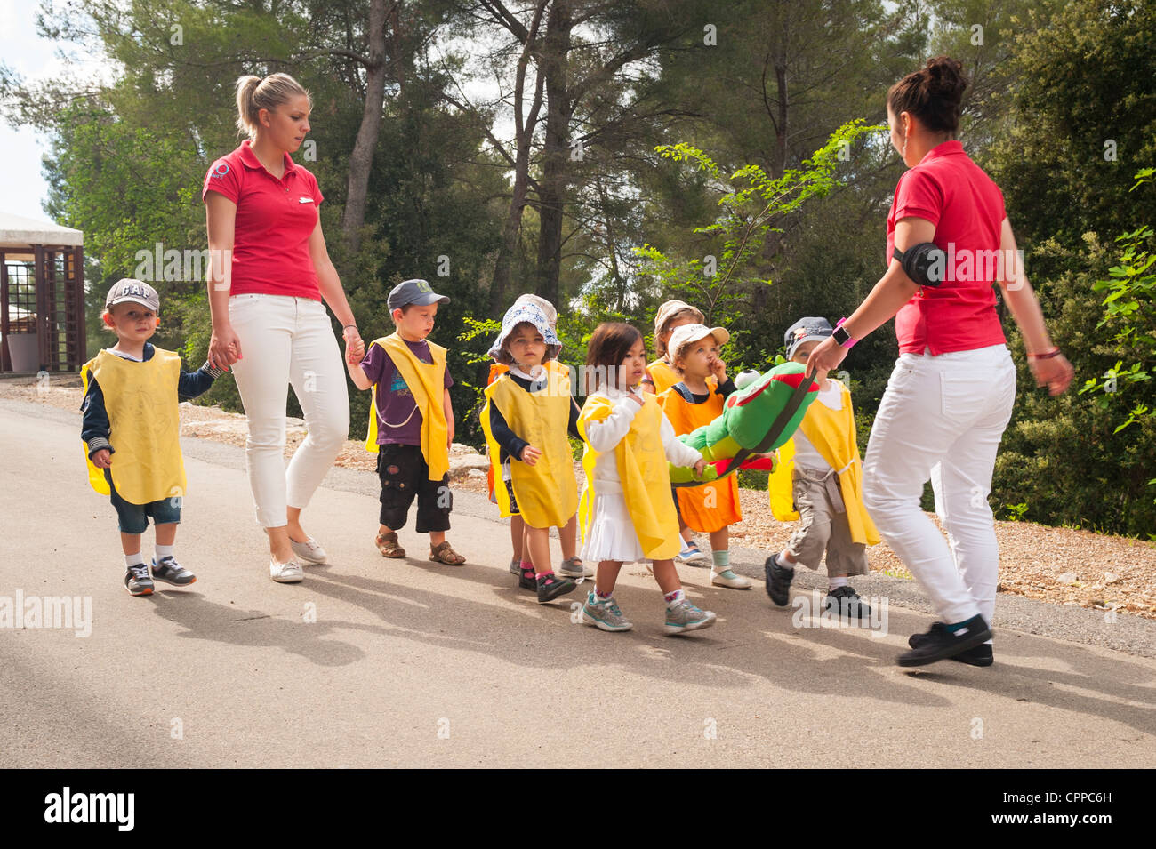 South of France , Province Club Med Opio baby toddler group escorted by GO's with kids in yellow overalls holding - Stock Image