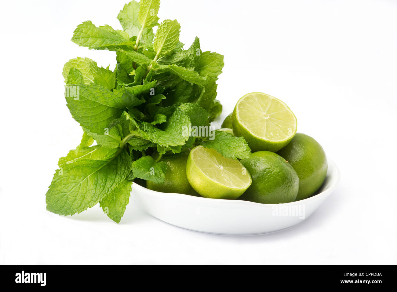 Bowl with limes and a bunch of mint on white background - Stock Image