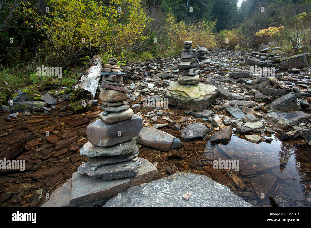 A couple of stacks of cairns accentuate the beauty of the small calm stream. - Stock Image