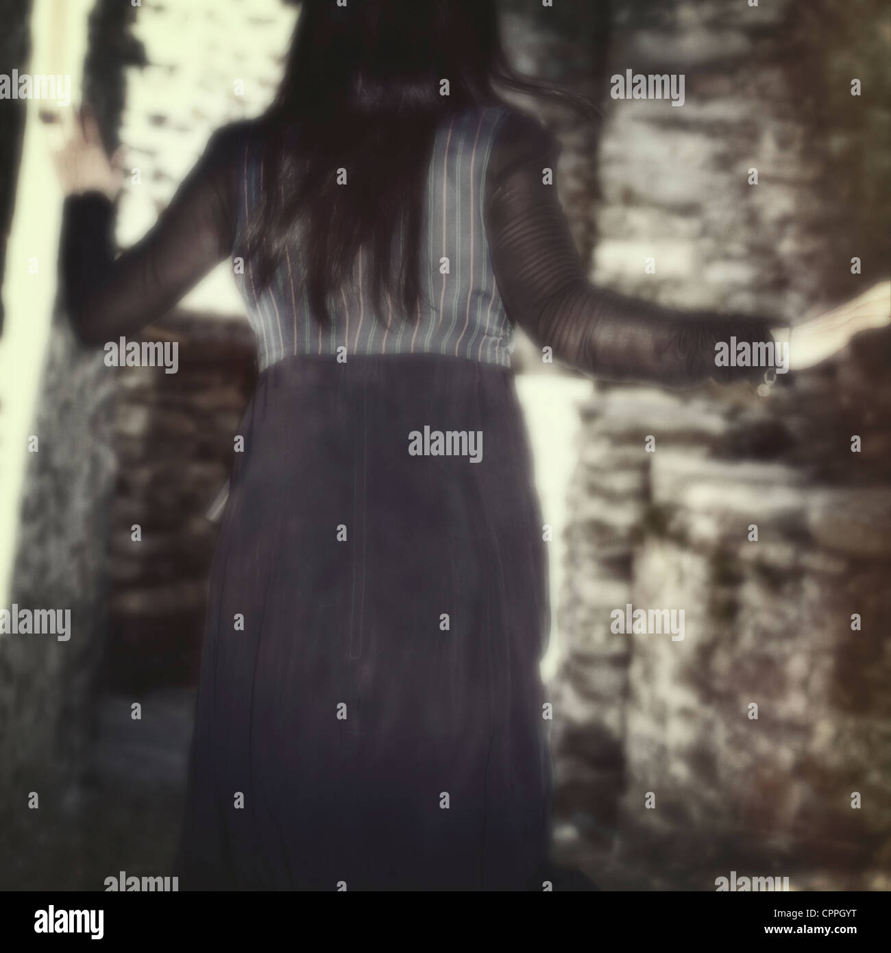 young woman is trying to escape and runs into a narrow alley - Stock Image