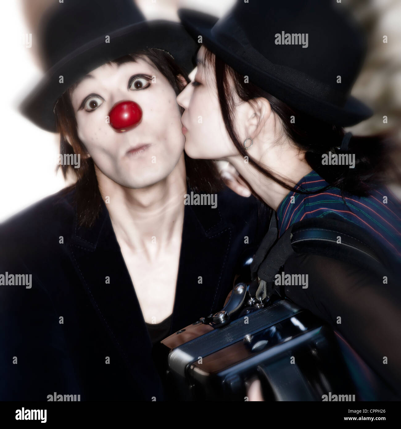 a couple of clowns - the woman kisses the man - Stock Image