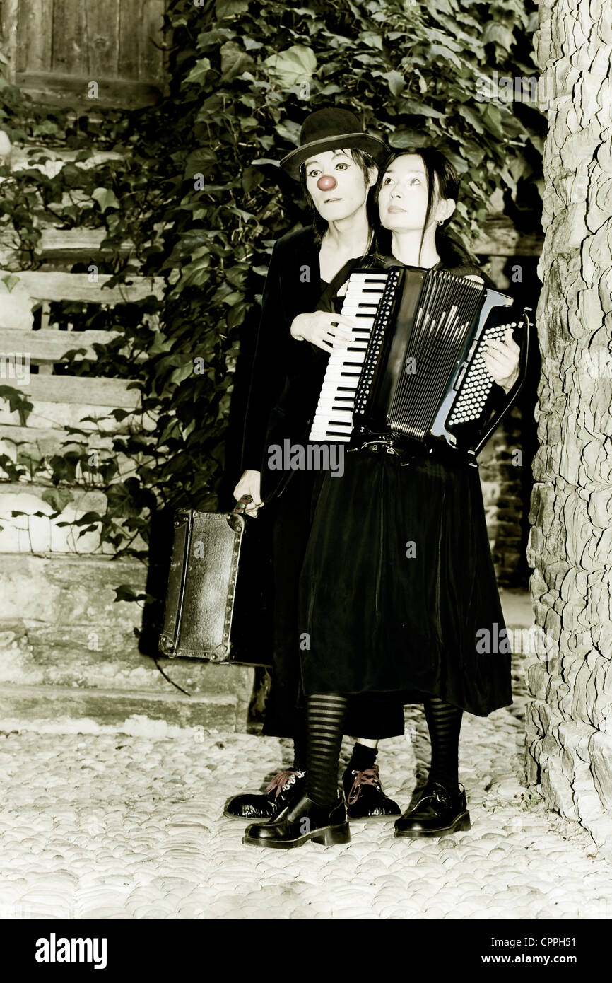 a couple of clowns is walking through an old, narrow street, the man has an old suitcase, the woman plays the accordion Stock Photo