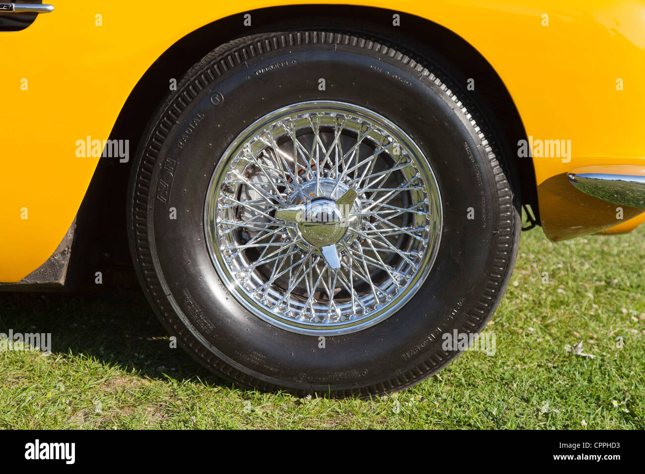 Yellow sports car chrome spoked wheel and tyre - Stock Image