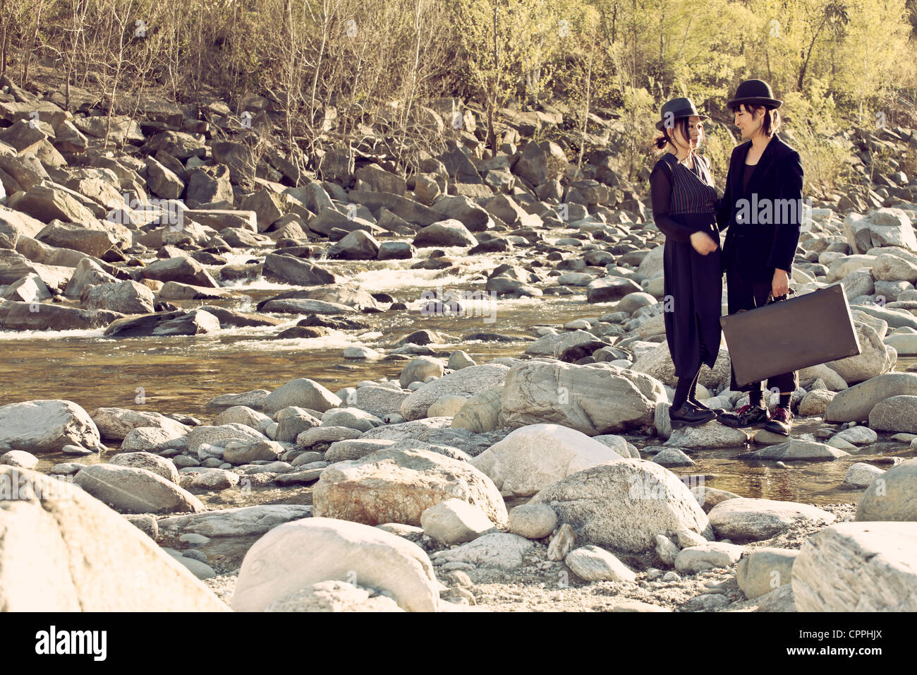 a man and a woman standing on rocks surrounded by a mountain stream - Stock Image
