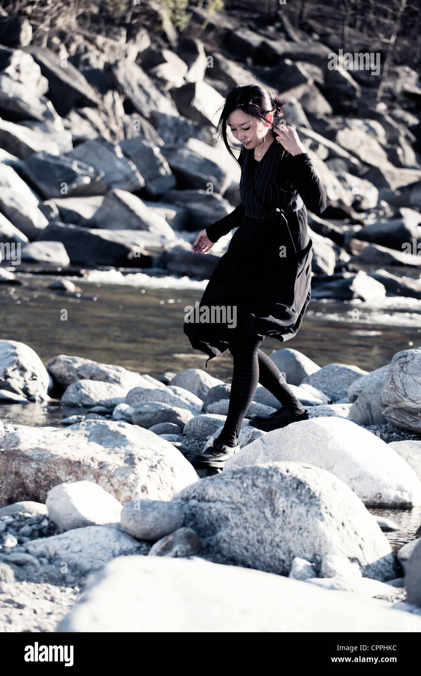a woman balancing on stones in a river bed Stock Photo