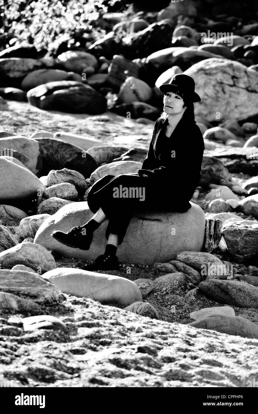 a tramp sitting on a rock in a river bed - Stock Image