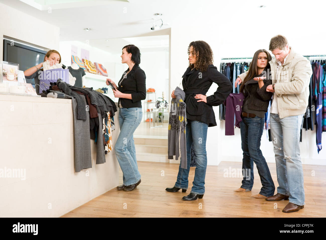 People queuing in a clothes shop - Stock Image