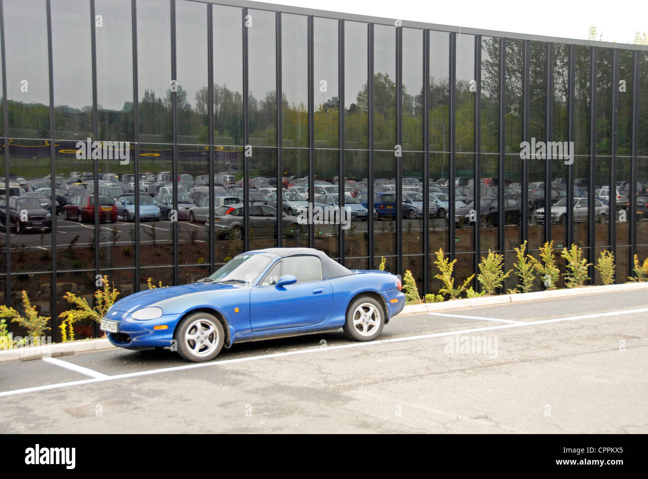 Cars in car park reflected in large glass window - Stock Image