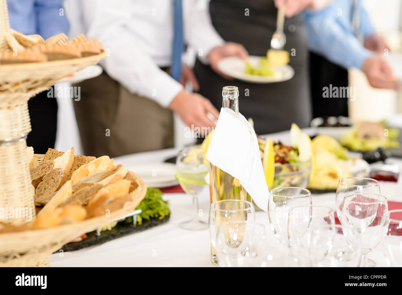 Business catering people serving themselves buffet at company meeting - Stock Image