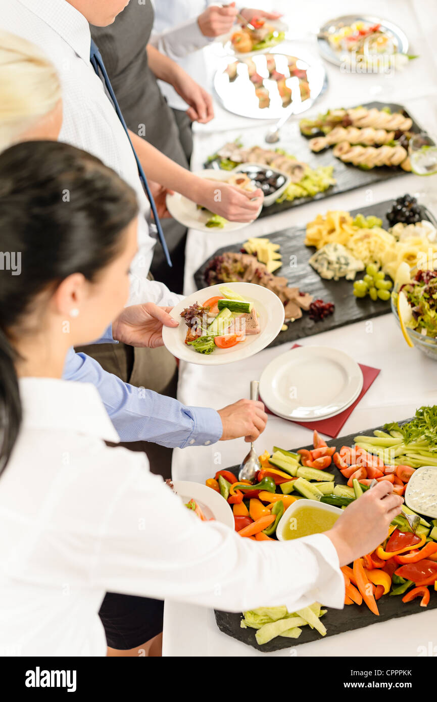 Business people around buffet table catering food at company event - Stock Image