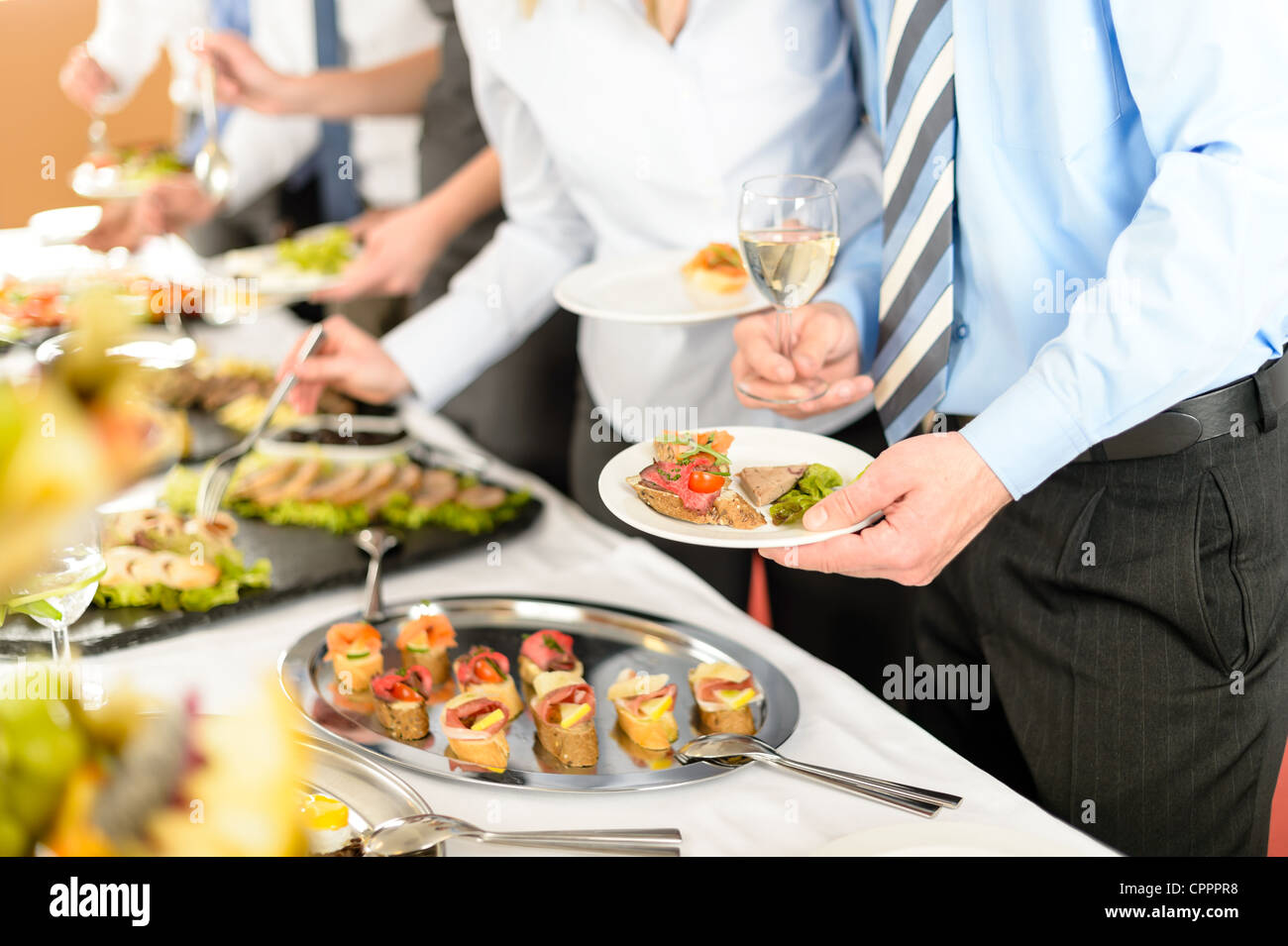 Catering at business company event people choosing buffet food appetizers - Stock Image