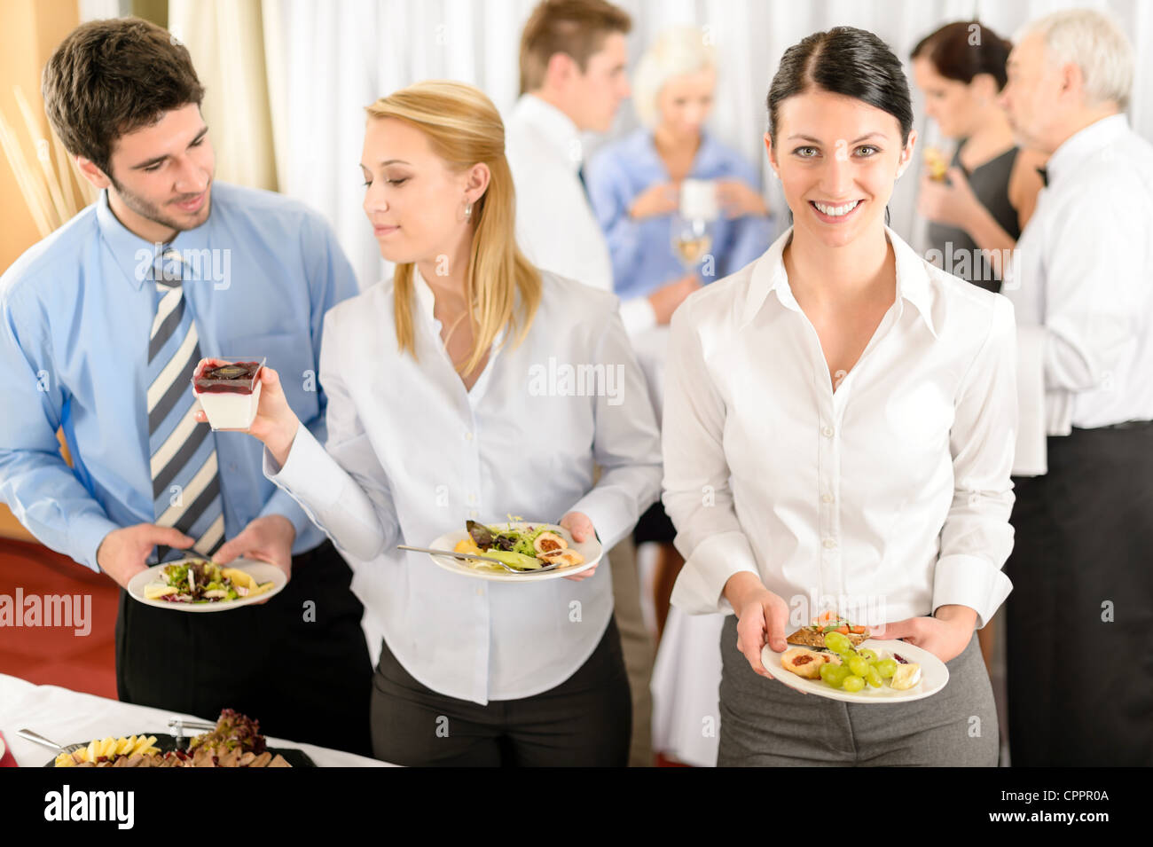 Business colleagues serve themselves at buffet catering service company event - Stock Image