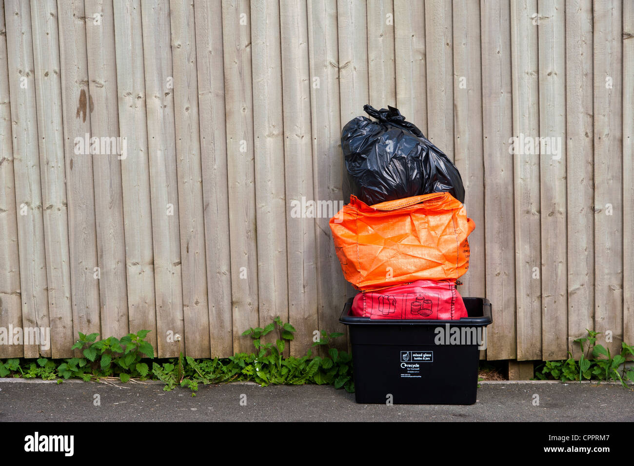 Household waste and recycling awaiting kerbside collection by Cornwall Council contractors, sorted into coloured Stock Photo