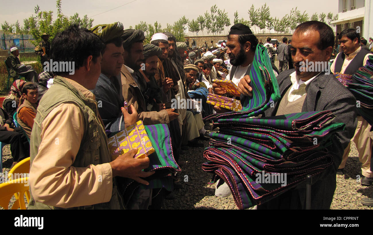 Former Taliban fighters receive copies of the Quran and chapans during a reintegration ceremony at the provincial - Stock Image