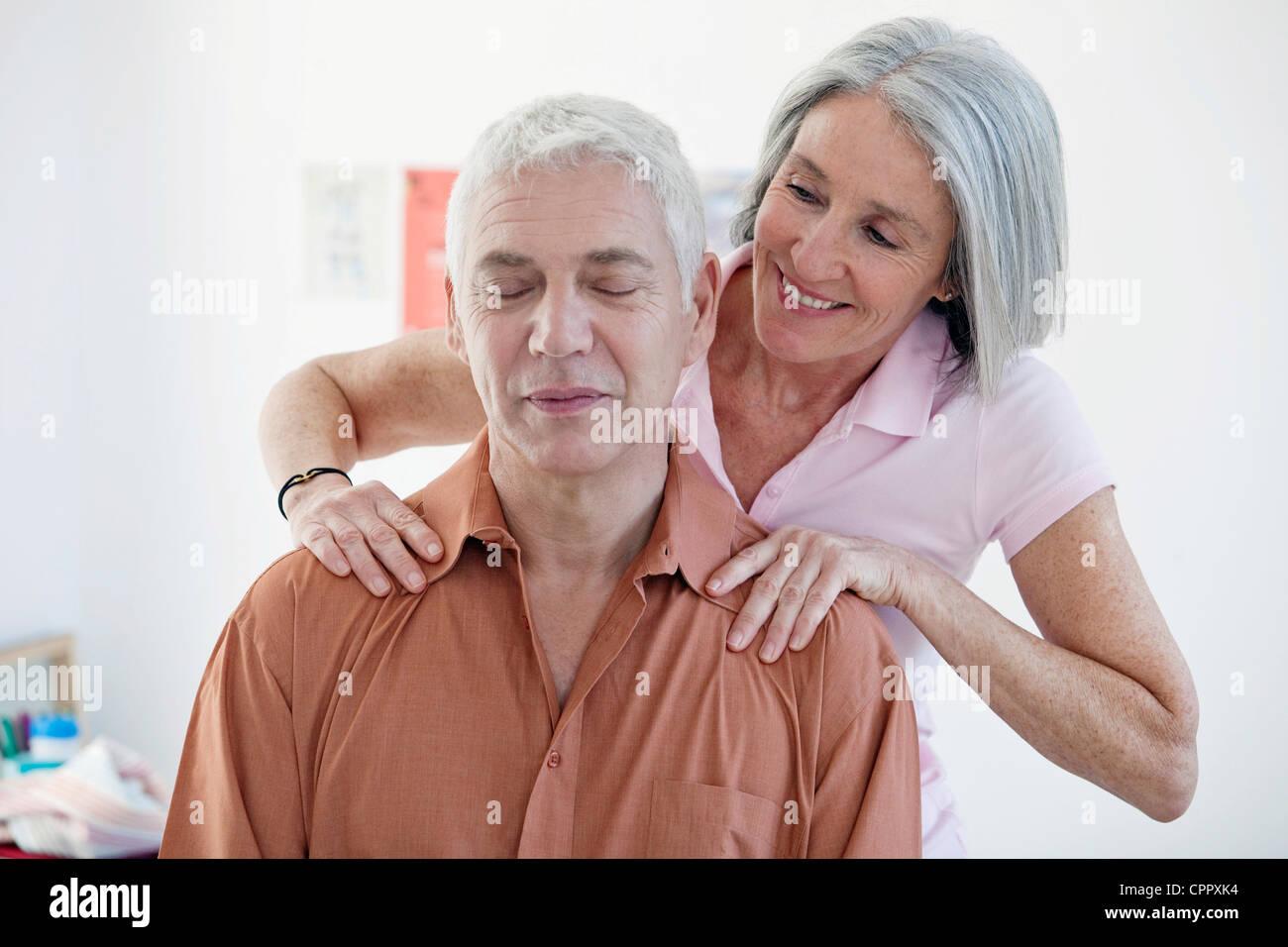 ELDERLY PERSON BEING MASSAGED - Stock Image