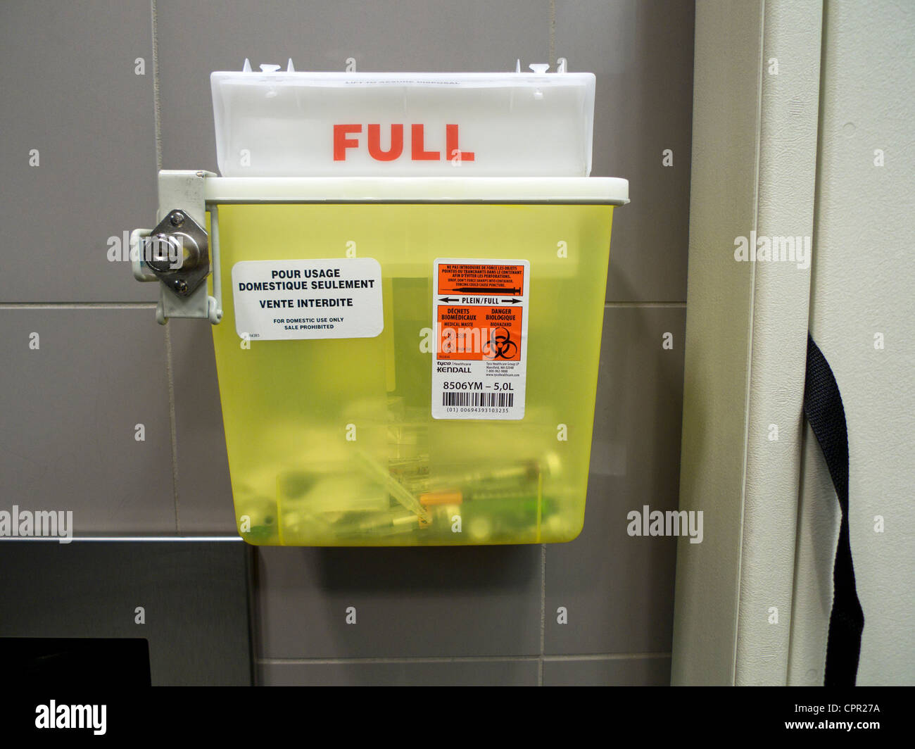 Disposal bin for diabetic hypodermic needles airport washroom Montreal Quebec Canada - Stock Image