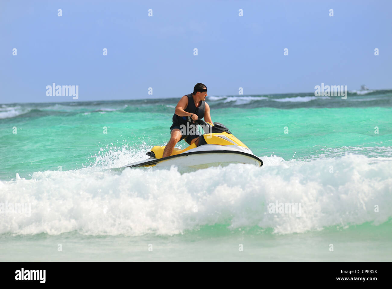 Man on Wave Runner turns fast on the water - Stock Image
