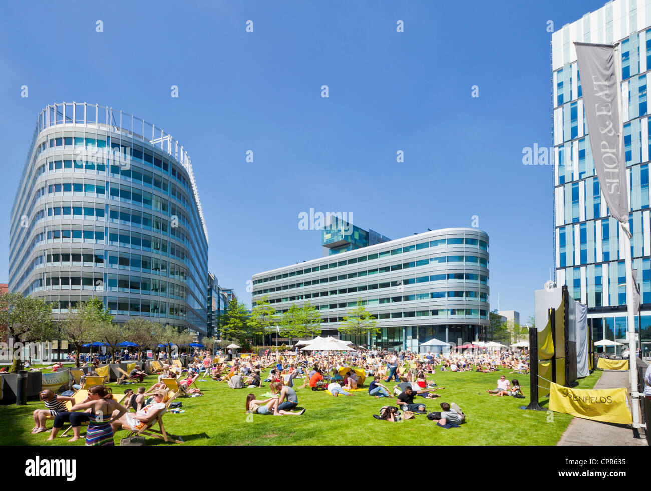 Crowds enjoying the hot weather and sunshine in the city centre Spinningfields  Greater Manchester England UK GB - Stock Image