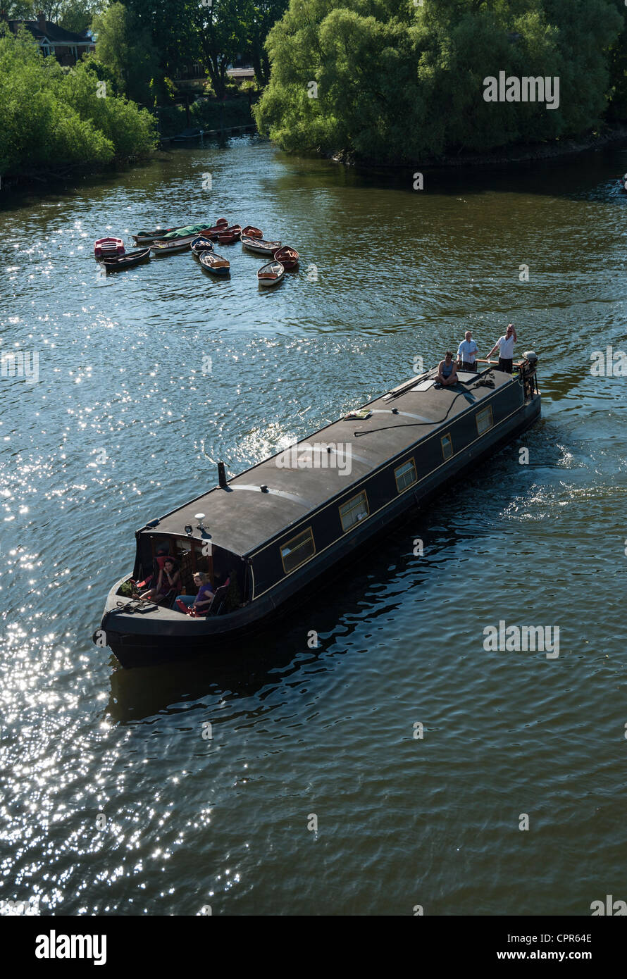 A long boat or barge and boats on the River Thames at Richmond London UK on a sunny summer day. Stock Photo