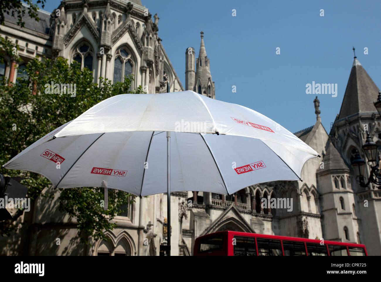 Sky News TV channel umbrella outside Royal Courts of Justice, London as Tony Blair appears at Leveson Enquiry - Stock Image