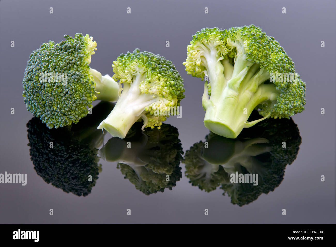 Studio image of fresh uncooked broccoli with reflection on black background - Stock Image