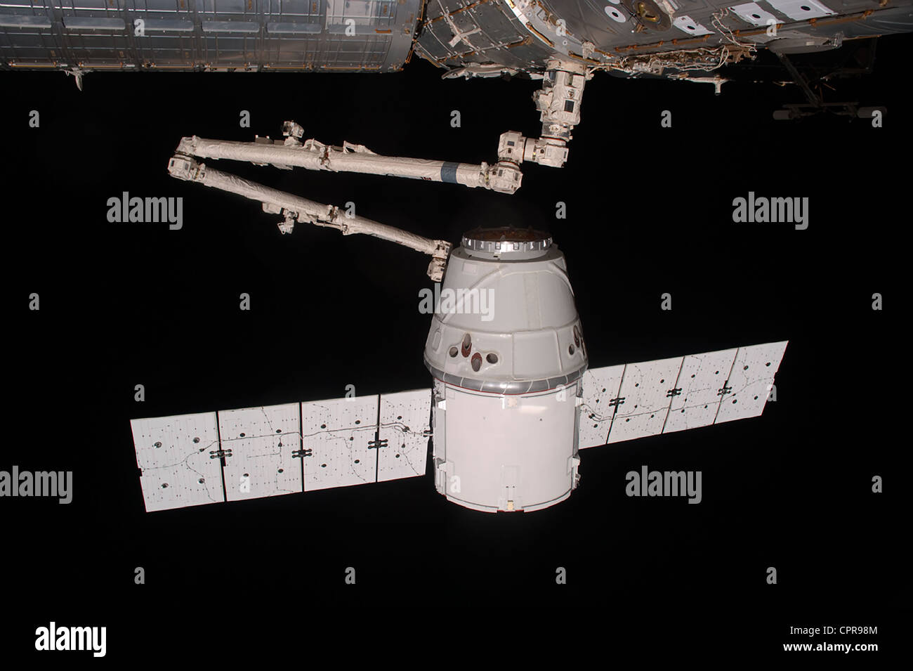 The SpaceX Dragon commercial cargo craft is grappled by the robotic arm at the International Space Station May 25, - Stock Image