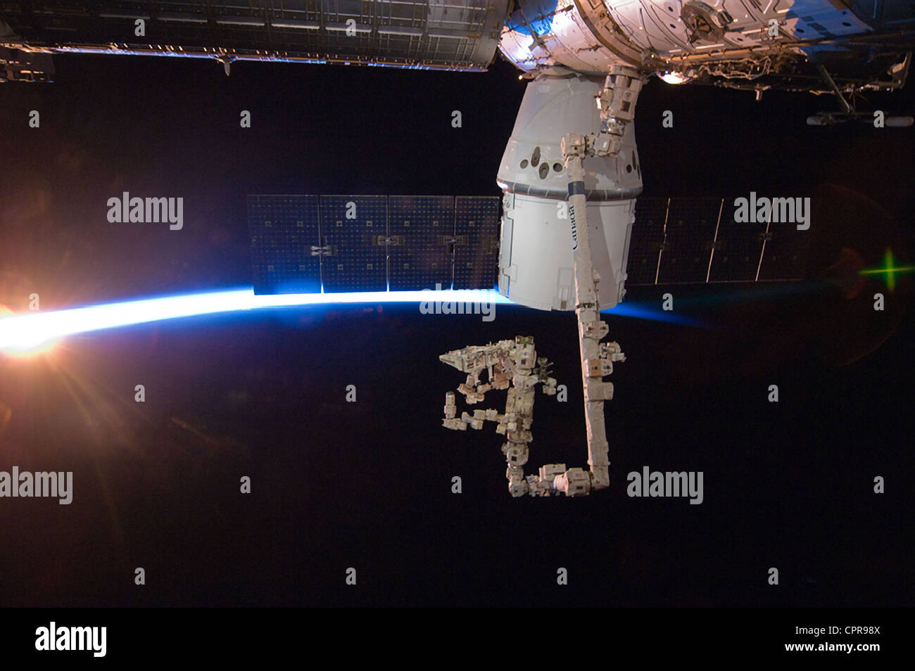 With rays of sunshine and the thin blue atmosphere of Earth serving as a backdrop the SpaceX Dragon commercial cargo Stock Photo