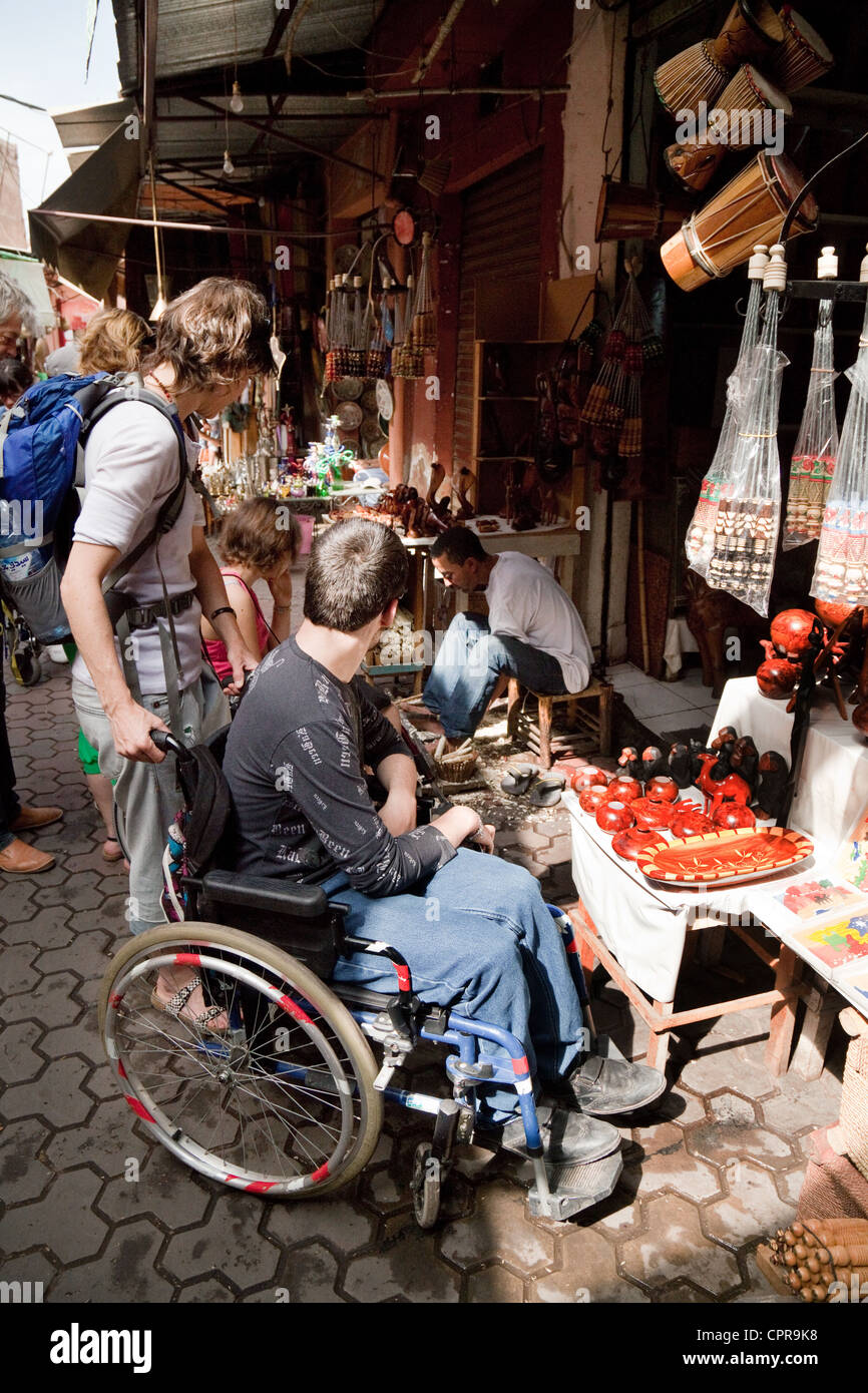 A disabled tourist in a wheelchair shopping in the souk, Marrakech, Morocco Africa - Stock Image