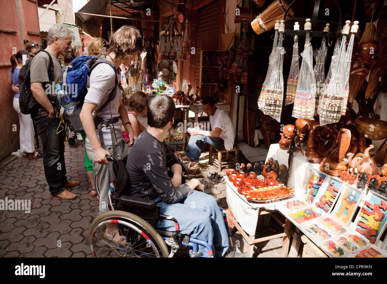 A disabled tourist in a wheelchair shopping in the souk or market, Marrakech, Morocco, Africa - Stock Image