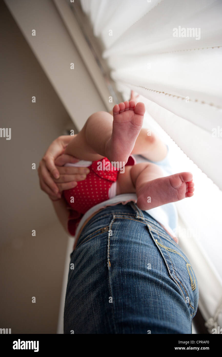 Low angle view of a mom holding her four month old baby girl, bottom of feet. - Stock Image