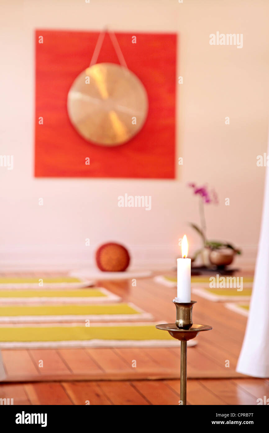 Large Gong, candle and orchid decoration in a yoga room - Stock Image