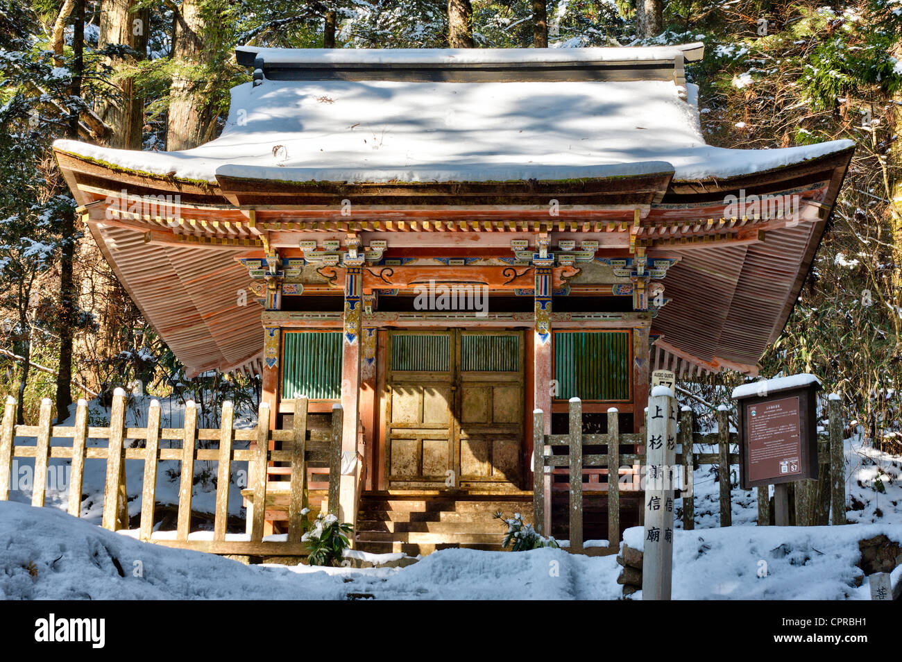 Japan, Koyasan, Okunoin cemetery. Snow-covered wooden painted Mausoleum hall marking the grave of Uesugi Kenshin. - Stock Image