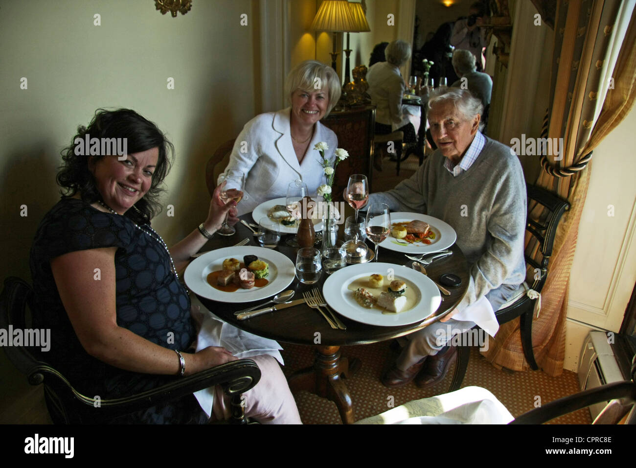 three diners in a restaurant, table set for four - Stock Image