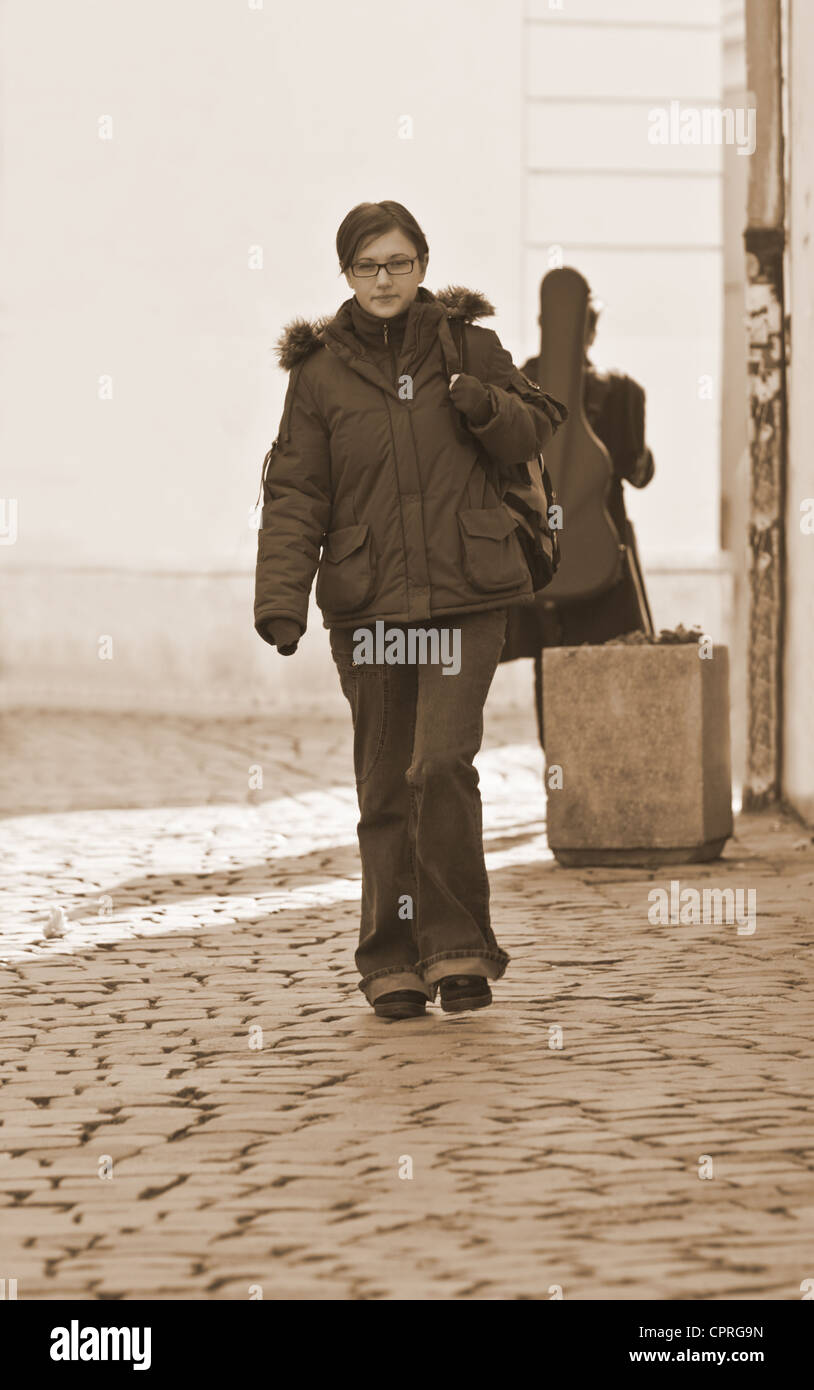 Redheaded girl student walking on a paved street-sepia tones. - Stock Image
