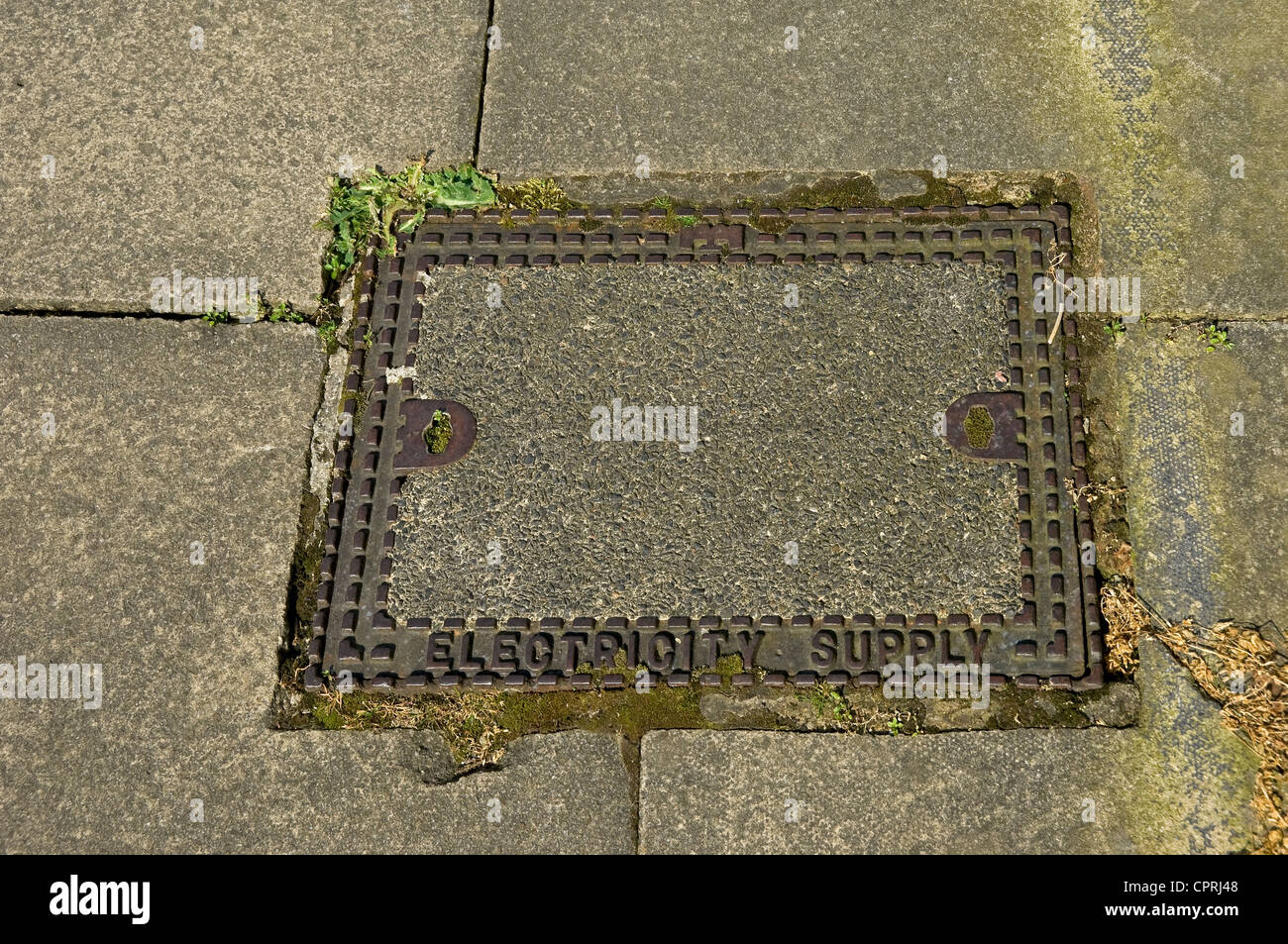 Manhole inspection lid cover set in pavement England UK United Kingdom GB Great Britain - Stock Image