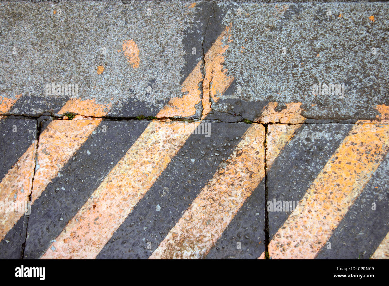 Painted paving slabs to warn of danger by edge of train station platform. - Stock Image