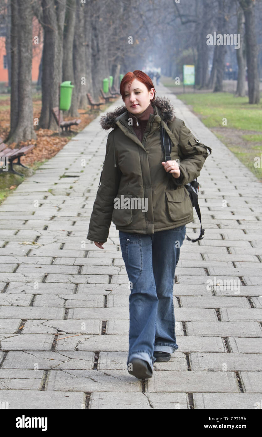 Redheaded girl walking alone in an autumn park. - Stock Image
